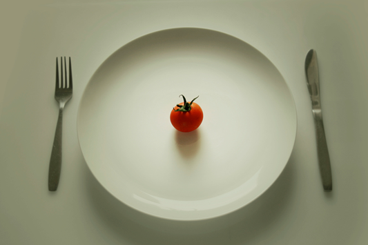 Plate with tiny tomato and nothing else.